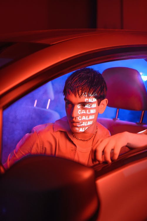 Serious young guy sitting in car at night