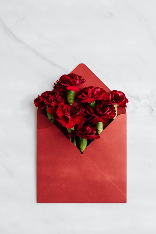 Red Flowers on Red Envelope Against White Surface