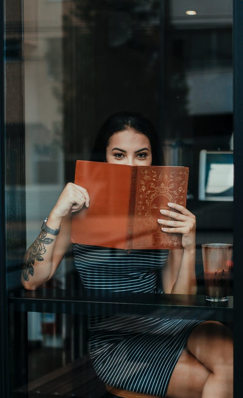 Through glass of unrecognizable positive young tattooed female resting in cafe and covering mouth with menu