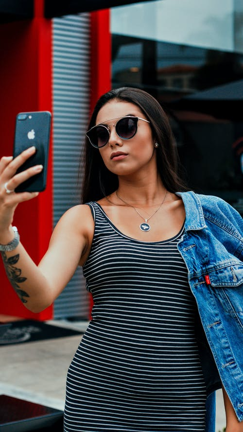 Confident young female taking self portrait on street