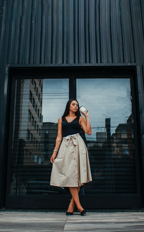 Full body of stylish young female with long dark hair in elegant outfit standing near entrance of modern building and drinking takeaway coffee