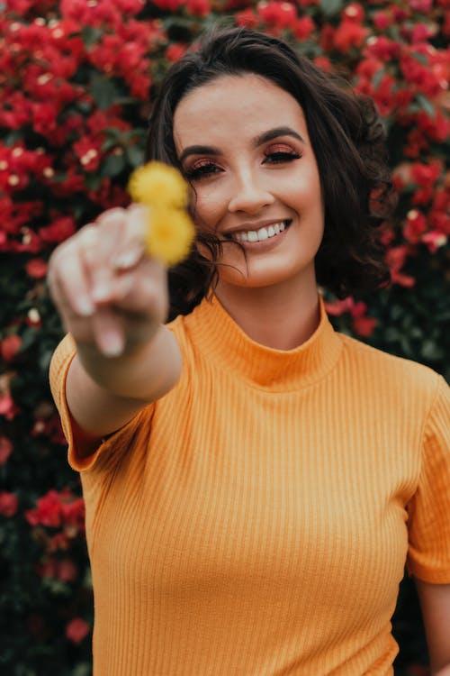 Photo of Woman Wearing Orange Top While Smiling