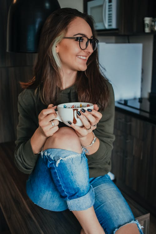 Photo of Woman Smiling While Holding Coffee Cup