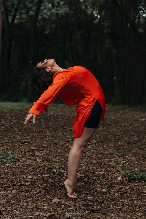 Photo of Woman Wearing Orange Long Sleeves While Bending Her Body
