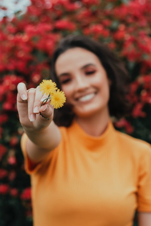 Shallow Focus Photo of Woman Holding Yellow Flowers
