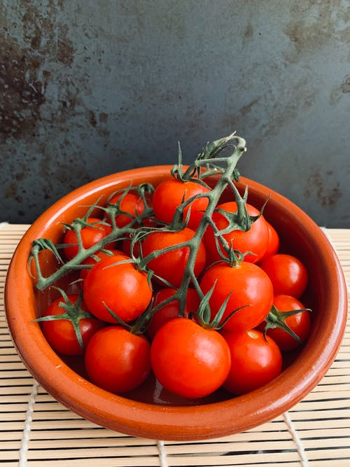 Bowl with ripe tasty tomatoes placed on table