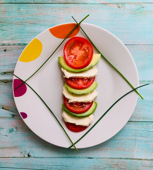 Sliced tomato and mozzarella served on plate with avocado and green herbs
