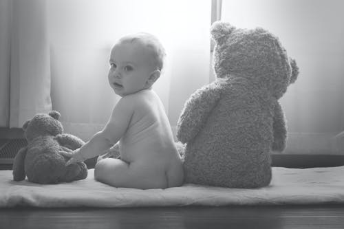 Gray Scale Photography of Toddler Sitting Between Teddy Bears