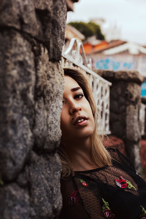 Side view of sensual young female in stylish outfit leaning on stone wall of ancient building and looking at camera while resting in countryside