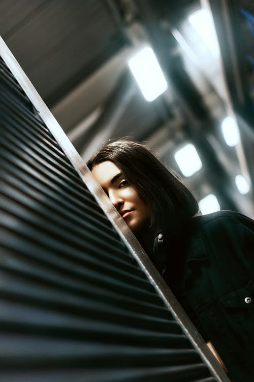Confident young ethnic lady hiding behind metal blinds in store