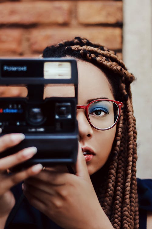 Trendy young ethnic lady photographing with retro film camera