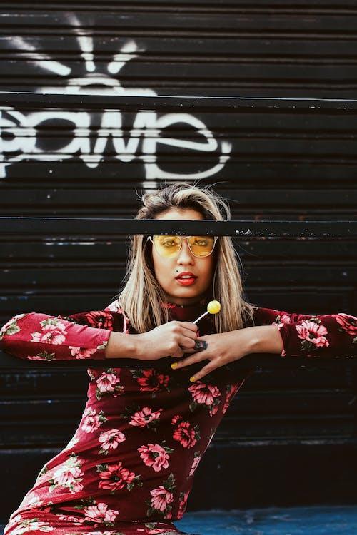 Stylish young woman eating lollipop on street