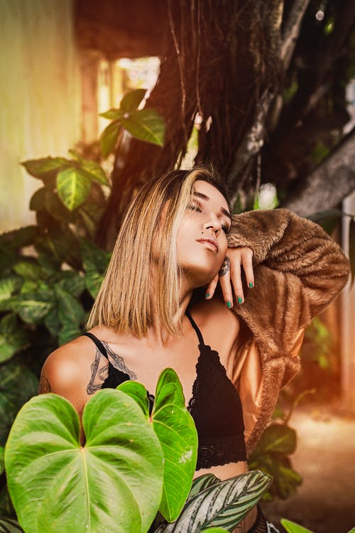 Alluring young woman enjoying summer vacation in garden with closed eyes