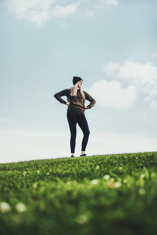 Woman in Black Tank Top and Black Pants Standing on Green Grass Field