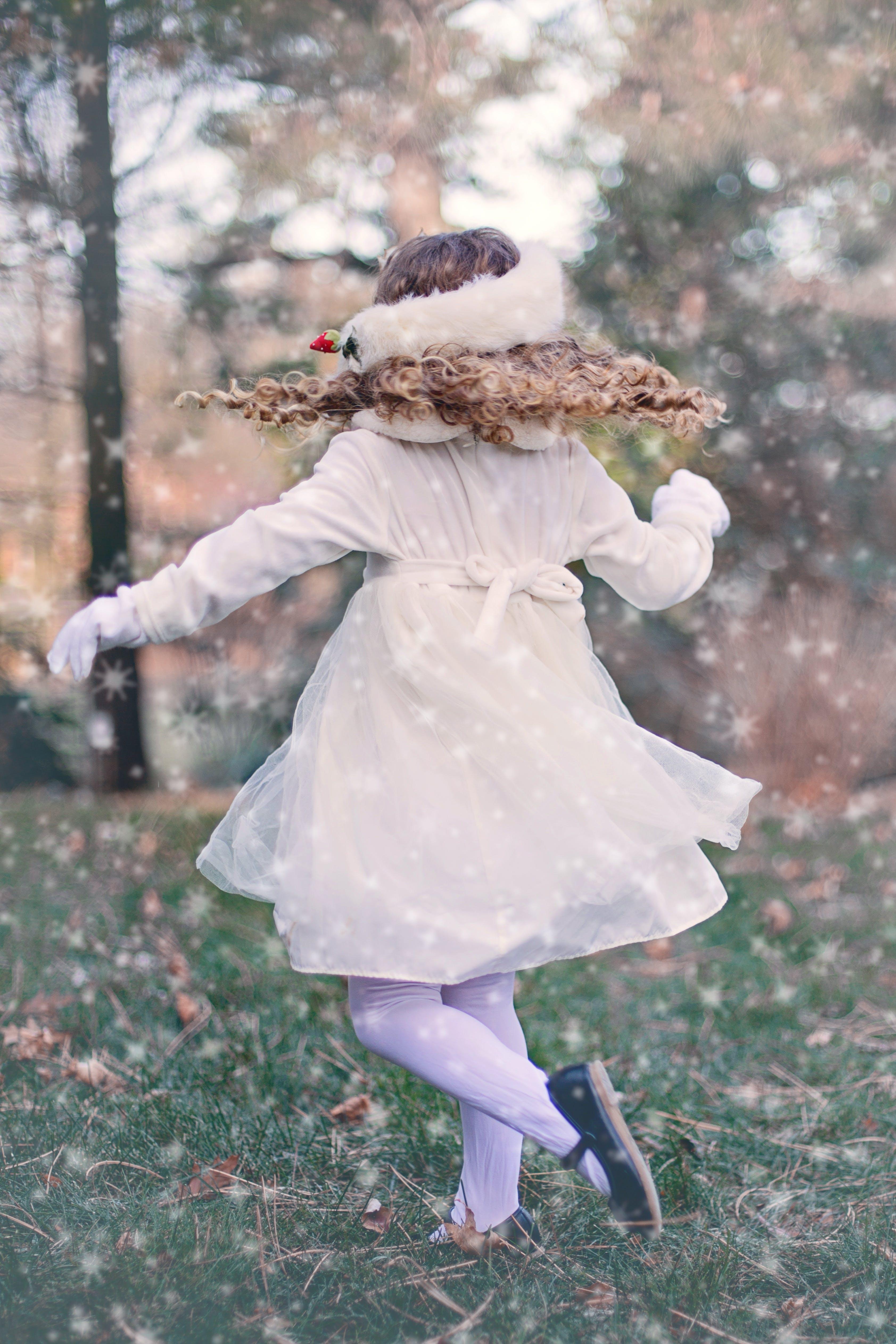 Girl Wearing White Long Sleeve Dress Standing on Green Grass Field
