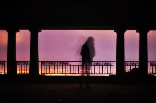 Anonymous person standing admiring cityscape at sunset from viewpoint
