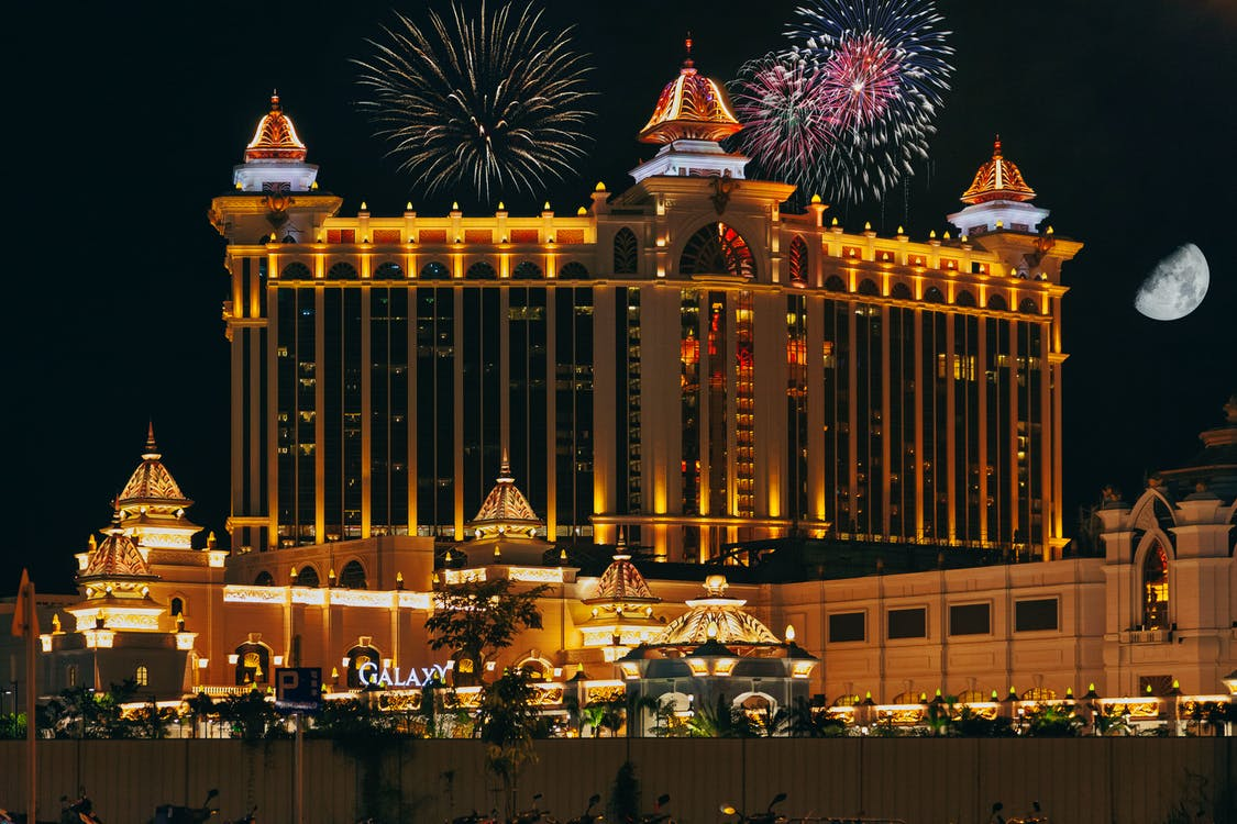 Colorful firework over famous modern palace with illuminated facade and square located in Macau at night