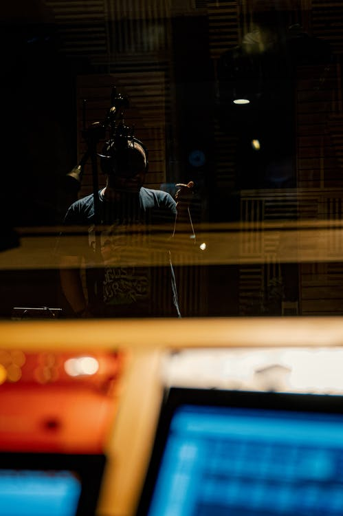 Through glass of musician in headphones recording song into microphone in modern music studio