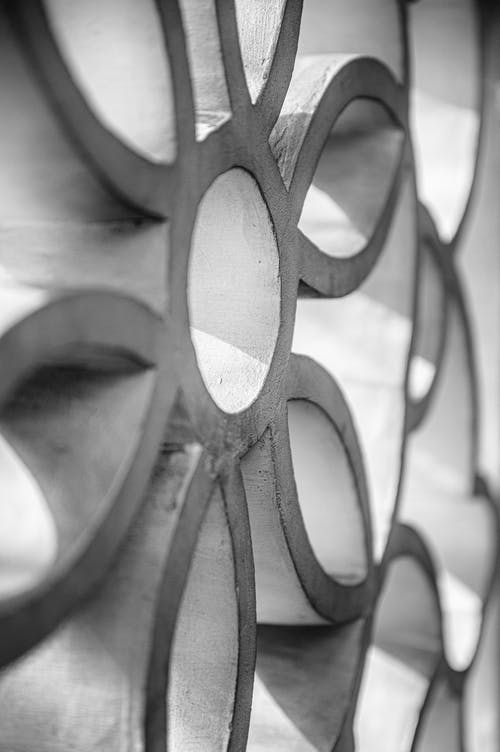 Black and white circular shape decoration with halls on fence made of metal details