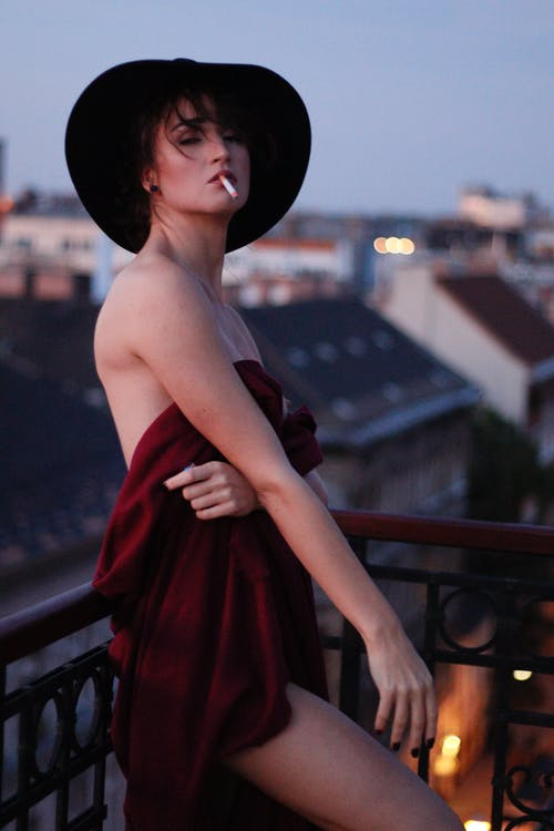 Stylish woman in hat with cigarette on balcony