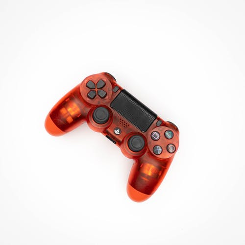 Top view of modern orange gamepad for game console placed on white background
