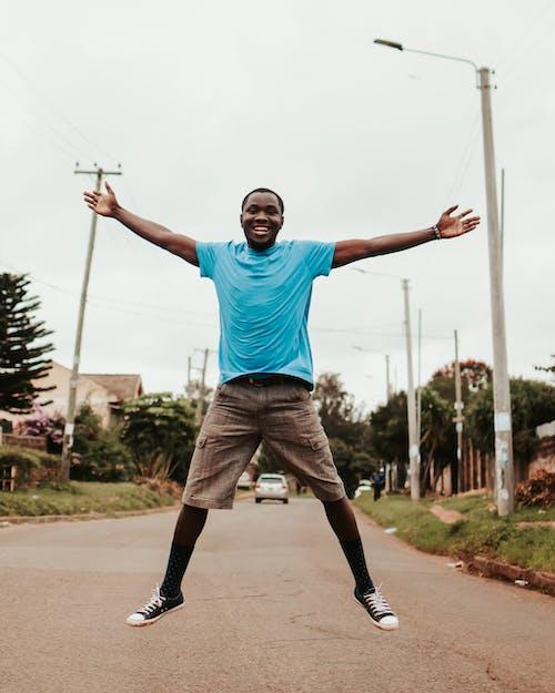 Black happy man jumping on street