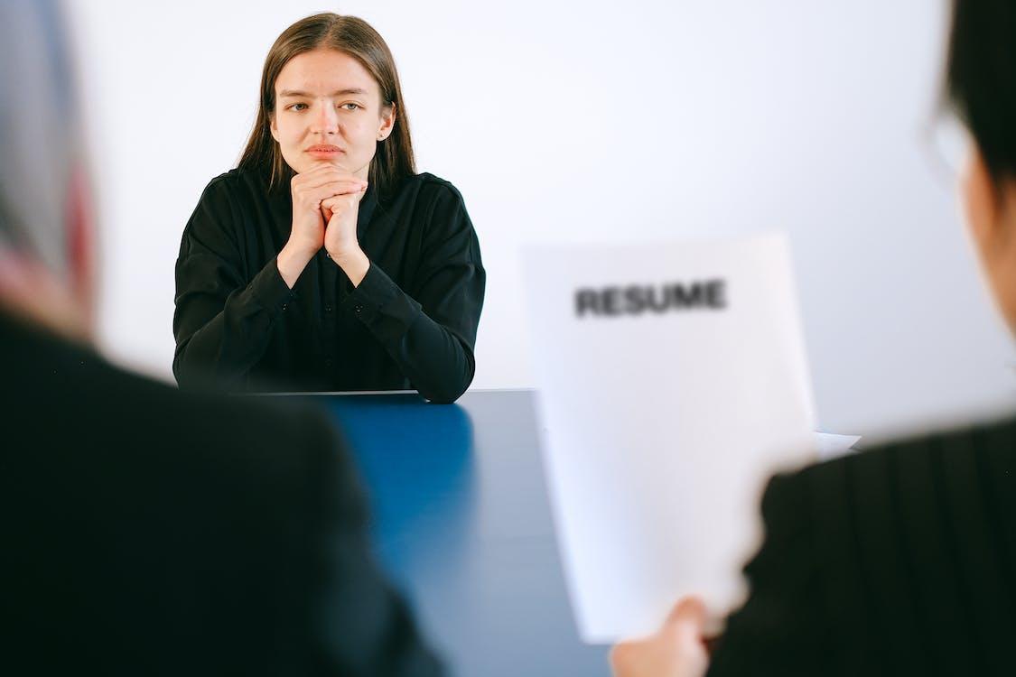 Woman in Black Long Sleeve Shirt Sitting Having Interview