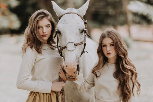 Stylish women standing near horse