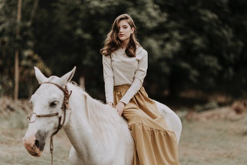 Graceful woman sitting on horse