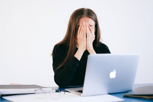 Woman With Hands on her Face in front of a Laptop