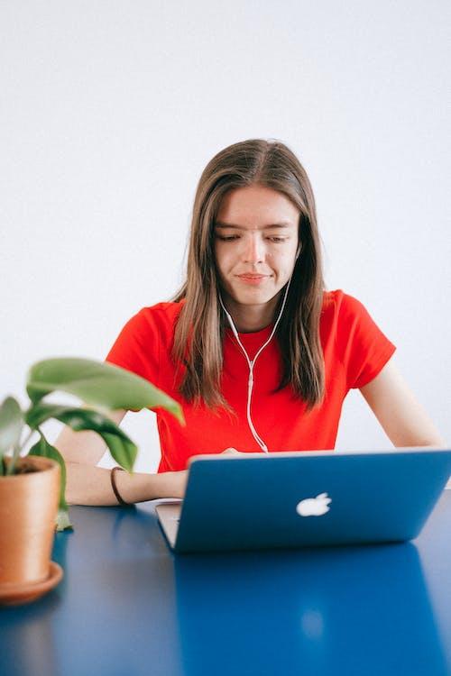 Kostnadsfri bild av 20-25 år gammal kvinna, ansiktsuttryck, bärbar dator, brunett