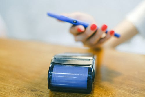 Person Holding Blue Pencil and Black and Silver Container