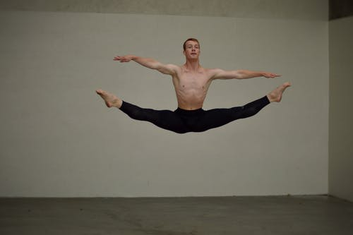 Flexible male dancer jumping in studio