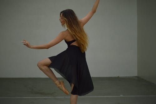 Back view of concentrated charming female ballet dancer with long sandy hair in black dress and pointe shoes performing in studio