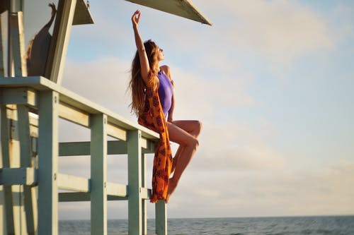 Slender woman in swimsuit resting on pier under roof
