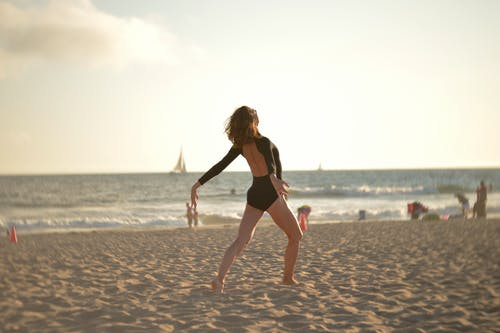 Full body back view of young expressive slender female dancer performing on sandy coast of wavy blue endless ocean in sunlight