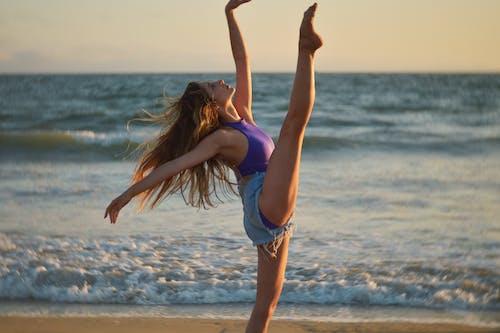 Beautiful ballerina dancing on shore of endless sea
