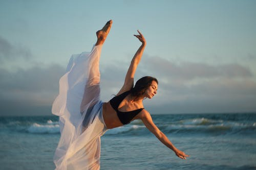 Flexible skinny barefoot slender female dancer outstretching arms and leg while showing dance move on coast of endless sea under blue sky covered with clouds
