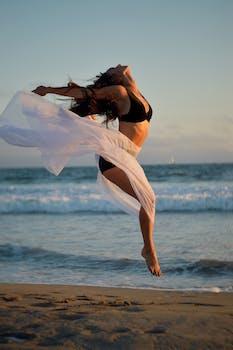 skinny dancer jumping over sandy shore of ocean