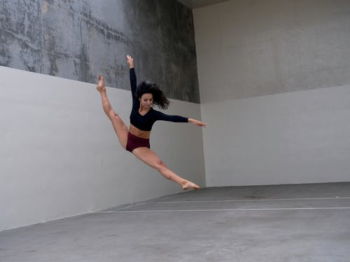 Full body of young concentrated ballerina in black crop top and purple underwear raising arms and outstretching legs while performing in simple studio with grey walls