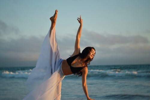 Concentrated female in black bra and white transparent skirt raising arm and leg while performing on coast of ocean under light blue evening sky