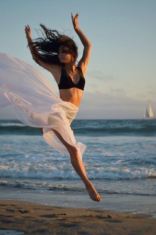 Flexible dancer rehearsing on shore of ocean