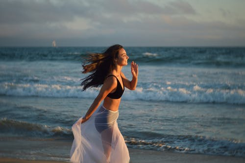 Side view of young happy female tourist with long dark hair in swimwear and pareo smiling and running on beach towards waving ocean during summer holidays