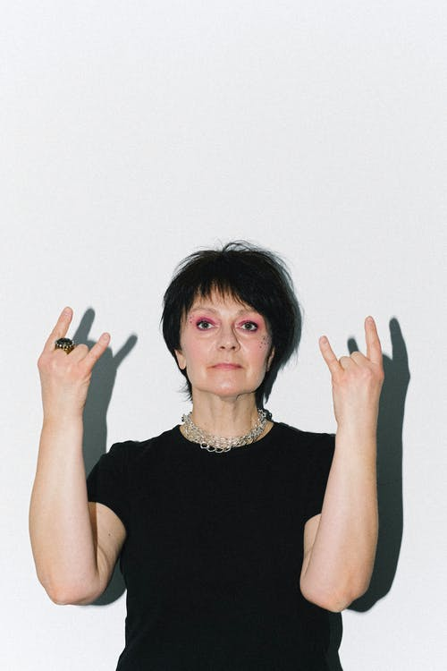 Woman in Black Tank Top Doing Peace Sign