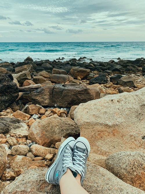Person Wearing Blue and White Sneakers Sitting on Brown Rocky Shore
