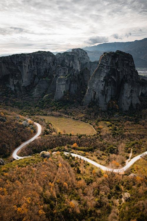 茶色のロッキー山脈の間の灰色のアスファルト道路