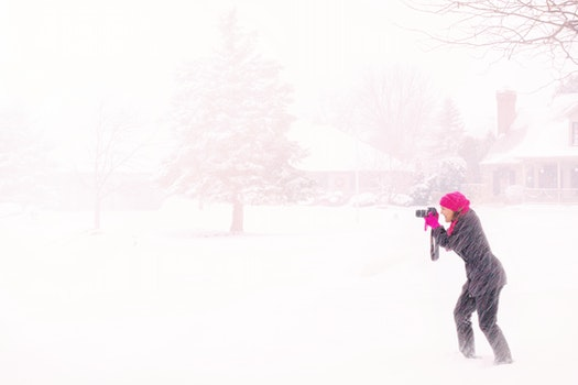 Woman in Pink Hijab Holding Black Dslr Camera Under Raging Snow during Daytime