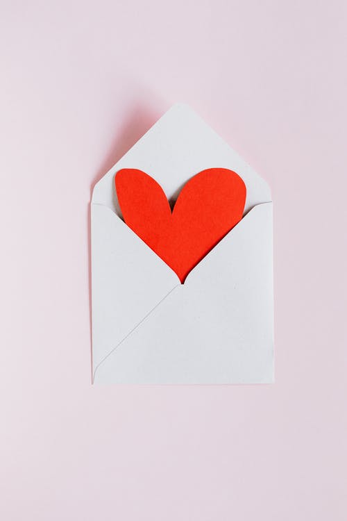 Top view of opened white envelope with handmade red paper heart placed against pink background as gift for Valentine day