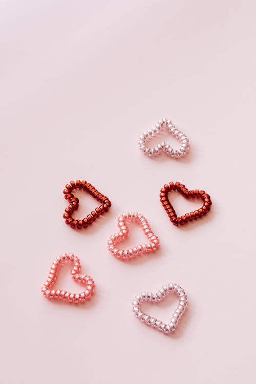 Top view of multicolored coil hair ties in shape of hearts composed on pink surface for Saint Valentines Day