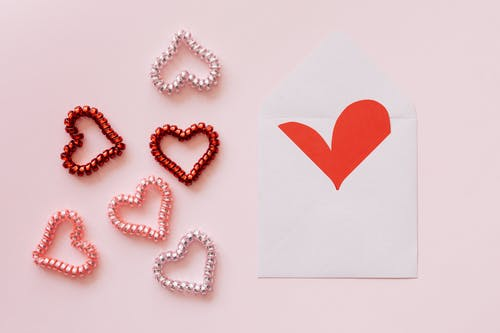 Collection of colorful decorative hearts near open envelope